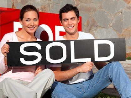 A happy young couple holding a sold sign in front of their new Atlanta home.