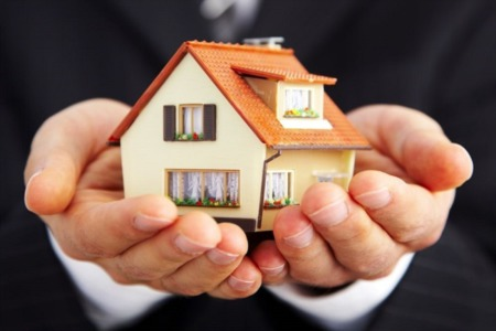 A Real Estate Agent Holds a Tiny House in His Hands Out to a Buyer