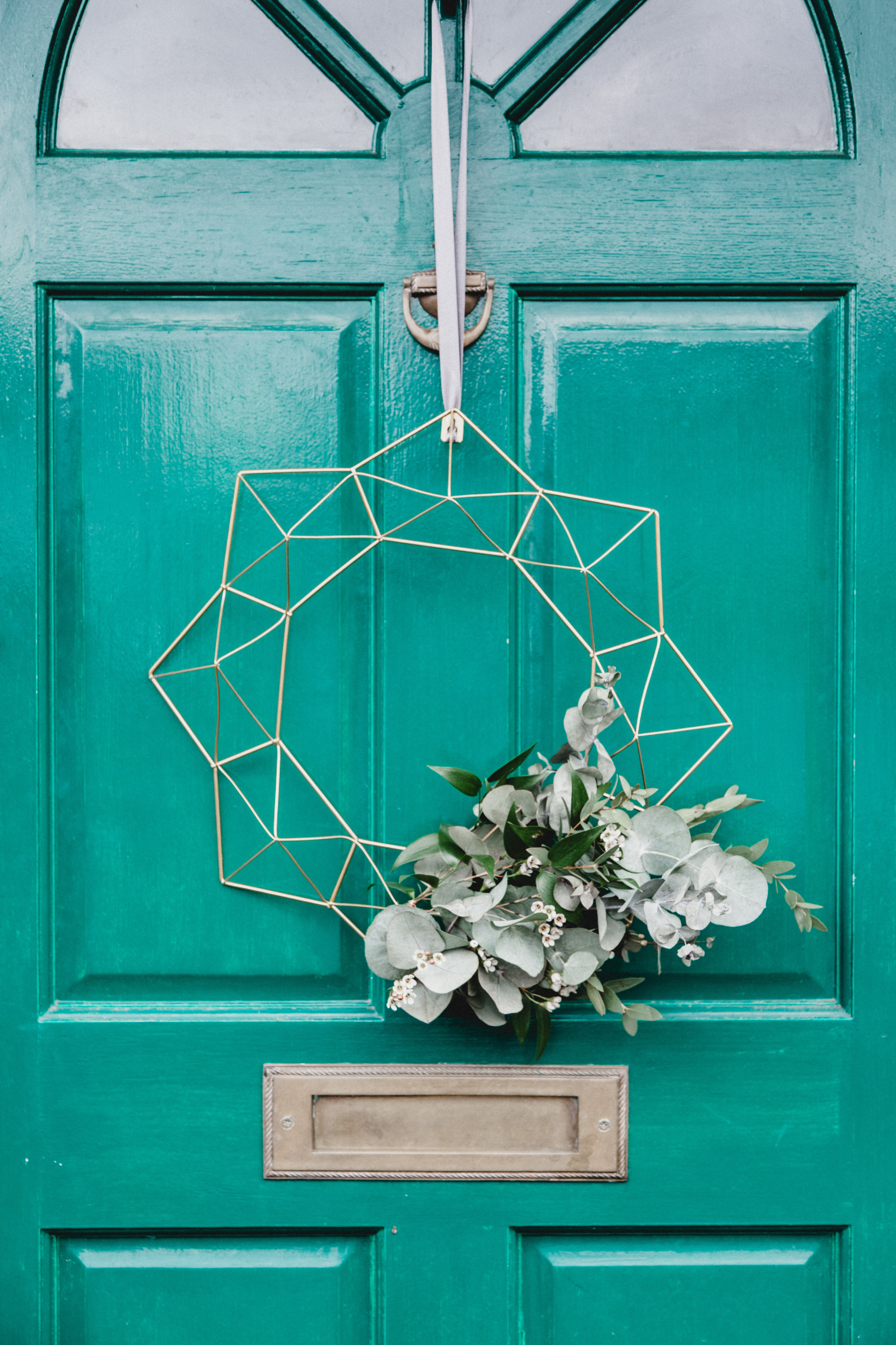 white wreath hanging on a green door