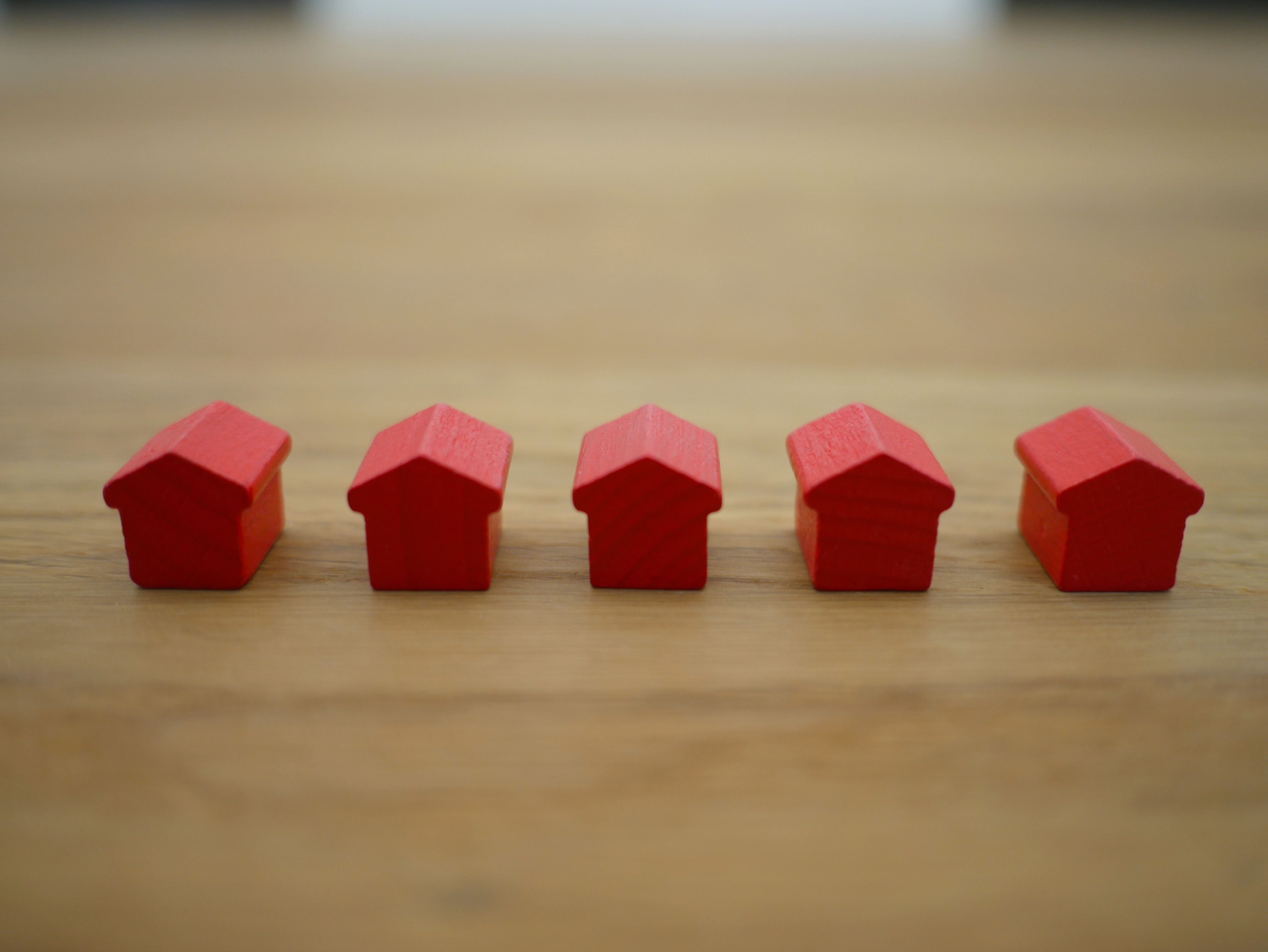 tiny red house figures on a table