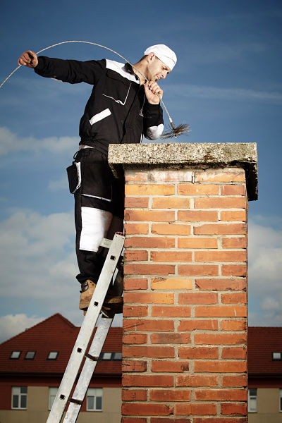 Professional chimney cleaner on ladder