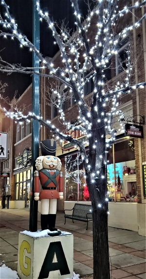 Christmas scene with wooden soldier standing under a lighted tree