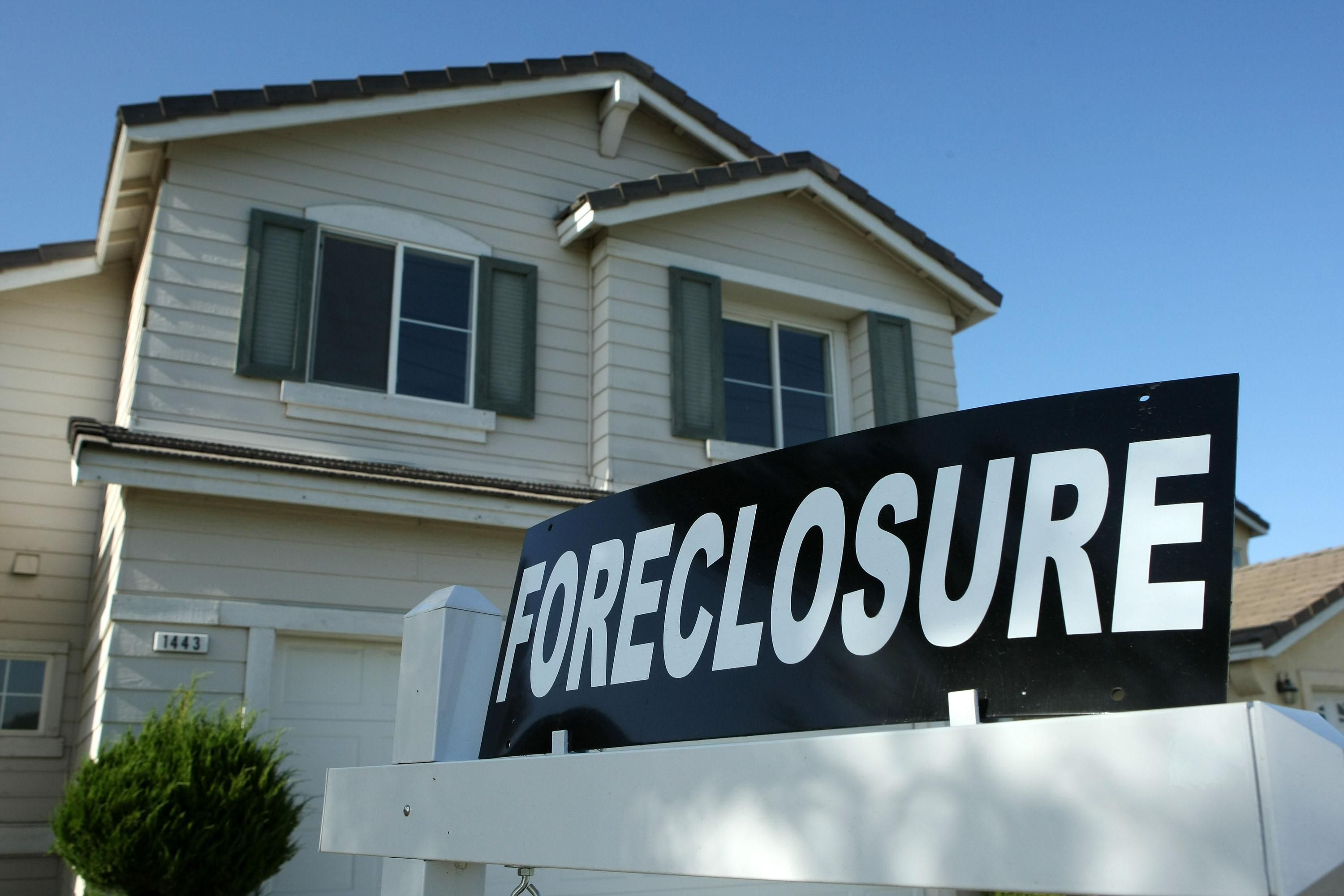 Home with a foreclosure sign in front