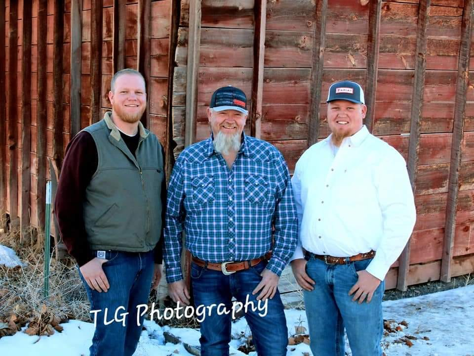 Three men standing in front of a red barn.