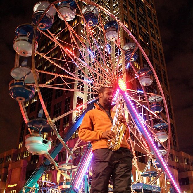 First Night Raleigh, NC - Man playing saxophone in front of ferris wheel