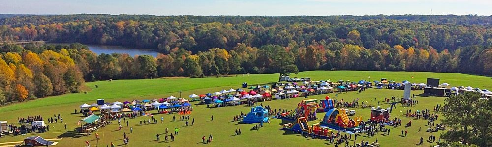 Hollyfest in Holly Springs, NC - Field with multi-colored tents and games with people walking