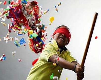 Cinco de Mayo Special Abilities Celebration - Child swinging stick at pinata with red blindfold on