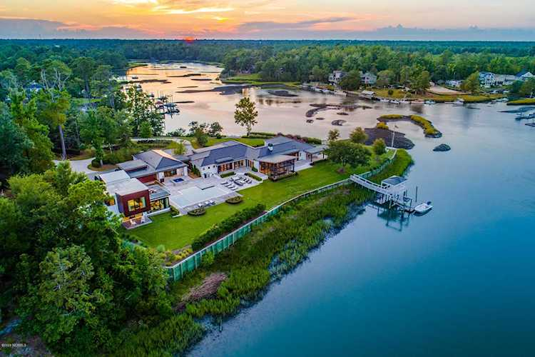 Aerial View of a Luxury Home on Creek with Sunset in Background