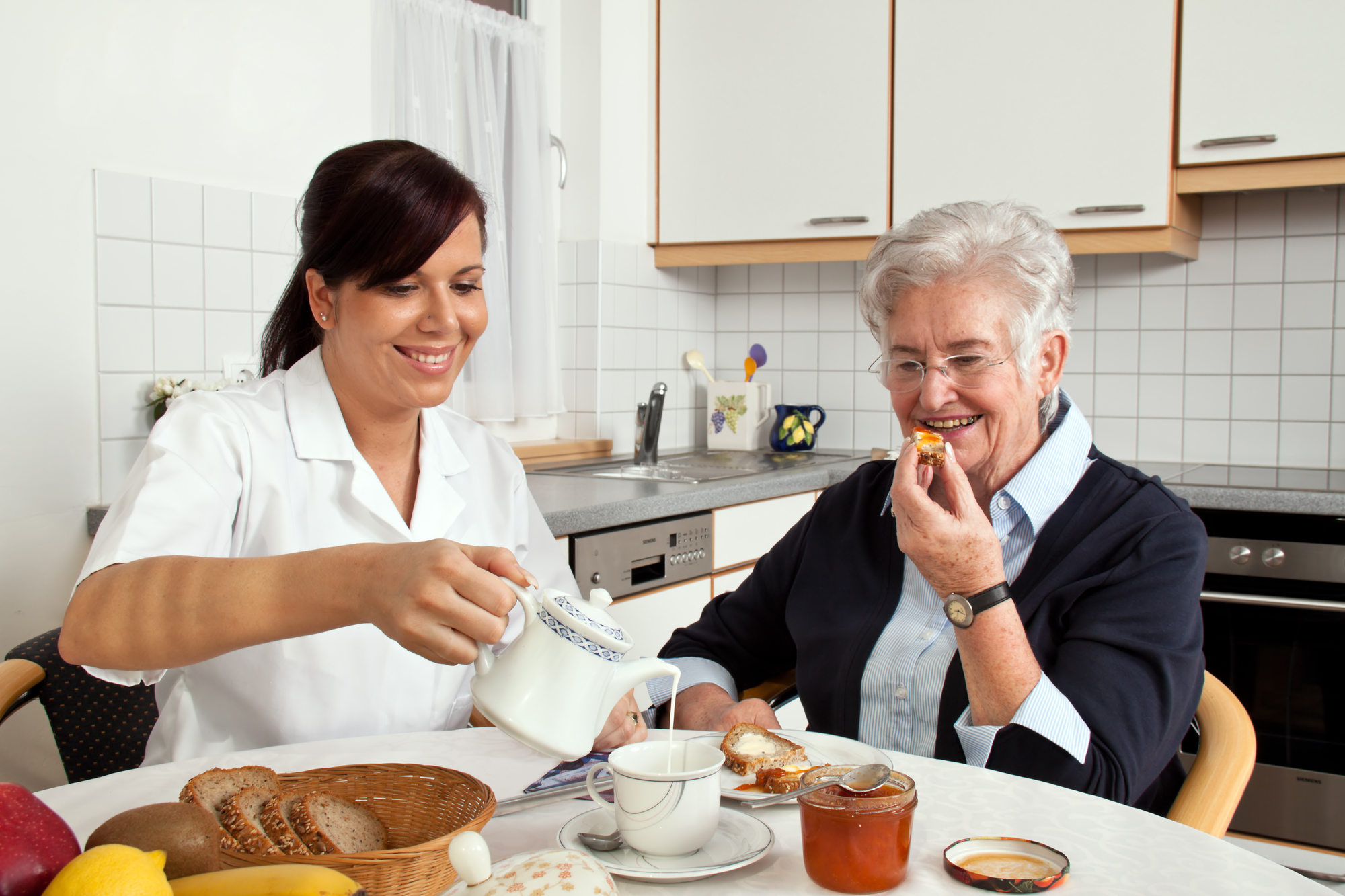 Two individuals sitting at a table in a home kitchen sharing breakfast; the younger person on the left pours cream into a teacup for a senior individual on the right, both smiling.