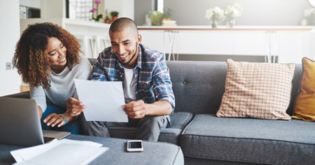 couple sitting on couch reviewing documents