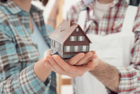 Picture of buyers holding a wooden model home