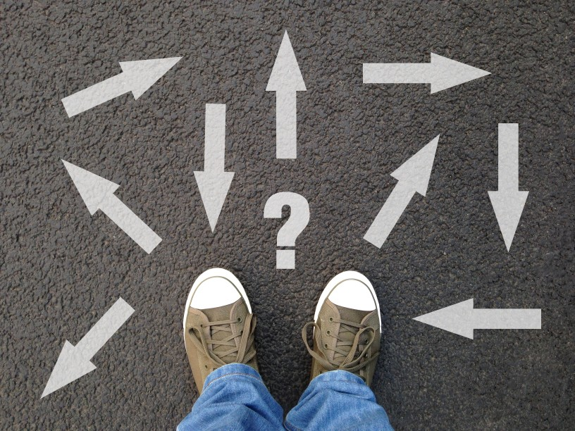 feet-standing-on-asphalt-with-multitude-of-arrows-in-different-directions-and-question-mark-confusion