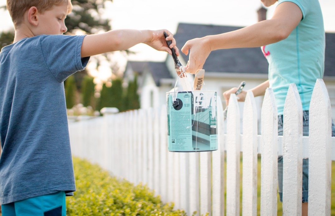 a-family-painting-a-white-picket-fence-in-the-summer