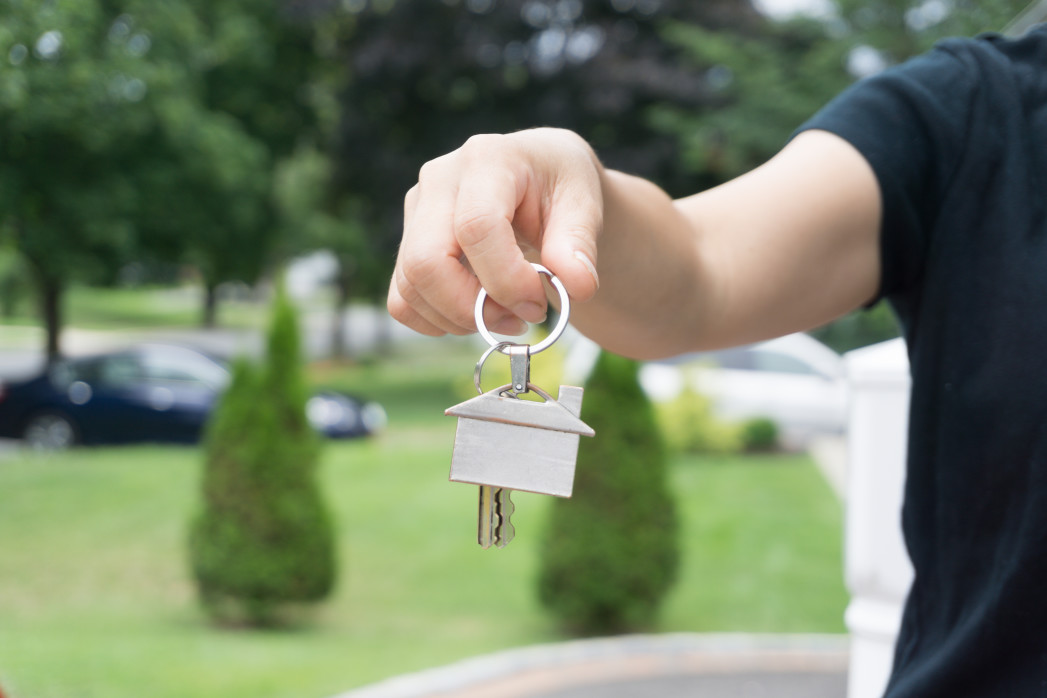 female-hand-holding-a-house-shaped-key-chain-and-keys-outdoor