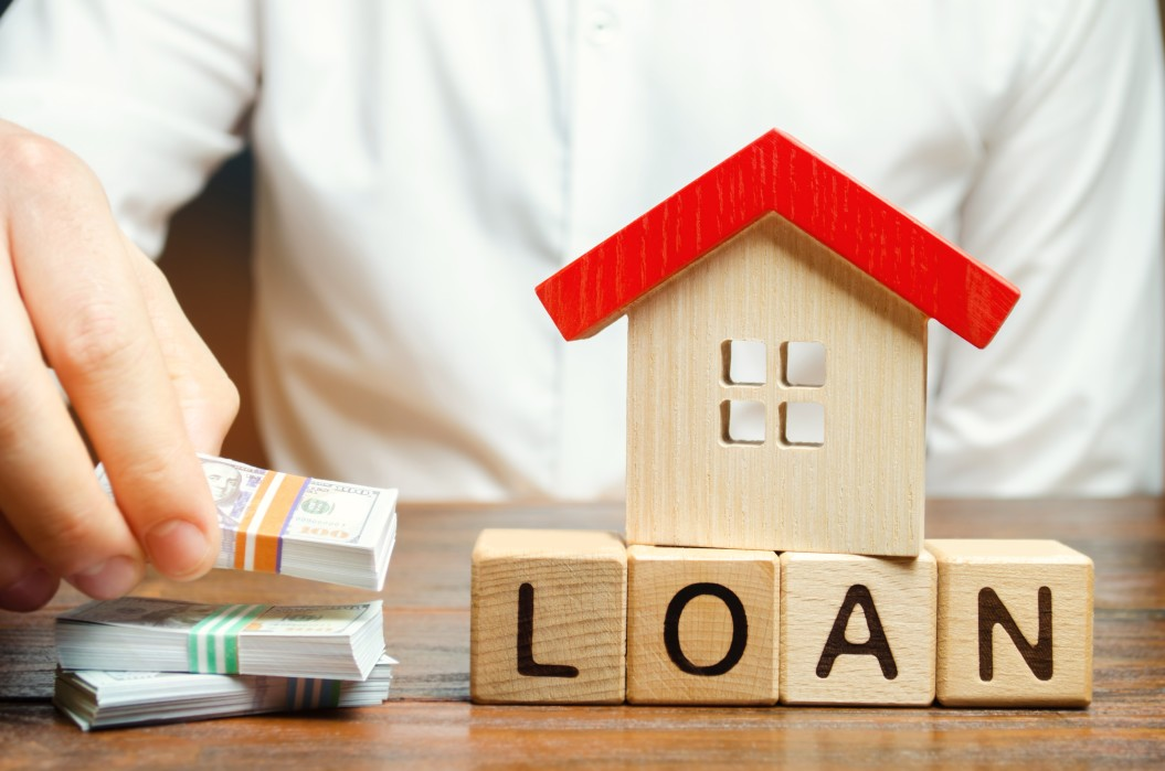 wooden-blocks-with-the-word-loan-house-and-money-in-the-hands-of-a-businessman-the-concept-of-buying