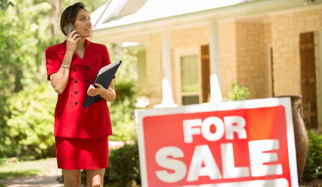 real estate agents talks on phone in front of for sale sign and house