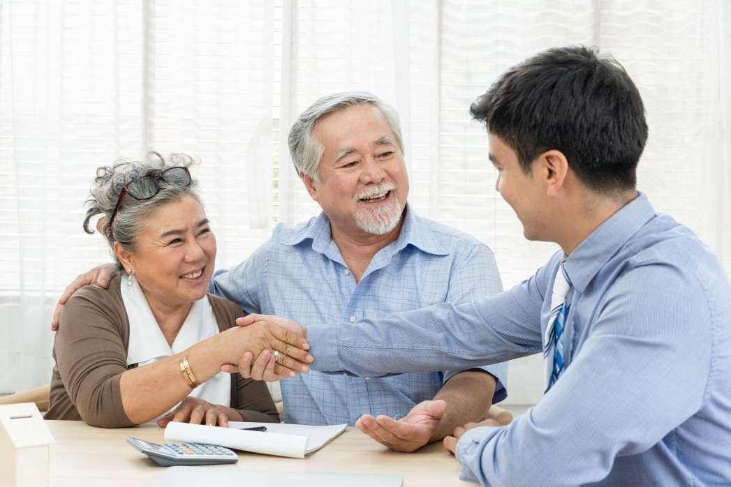 happy-smiling-asian-old-couple-making-purchase-and-mature-woman-handshake-with-real-estate-agent