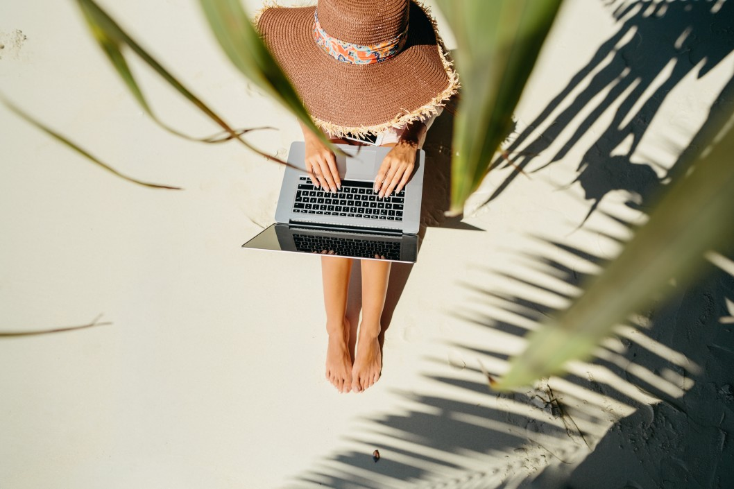 woman-freelancer-travel-and-working-on-the-beach-working-remotely-on-the-laptop-computer-through-the