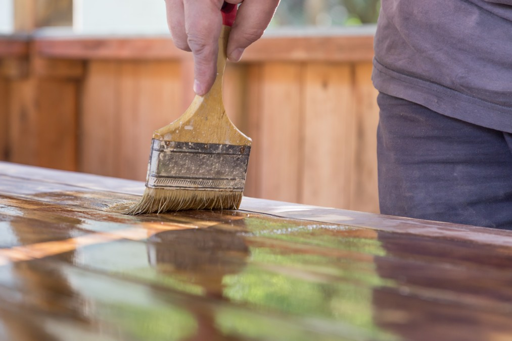 man-varnishes-a-wooden-table-paint-plank-hand-paintbrush-varnish-construction-wooden-renovation