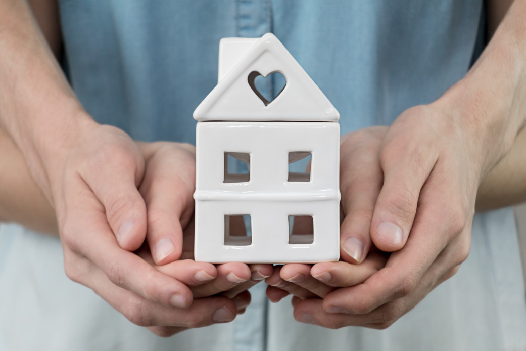 young-family-is-holding-toy-house-in-hands-cozy-man-people-home-finance-property-buy-sale-concept