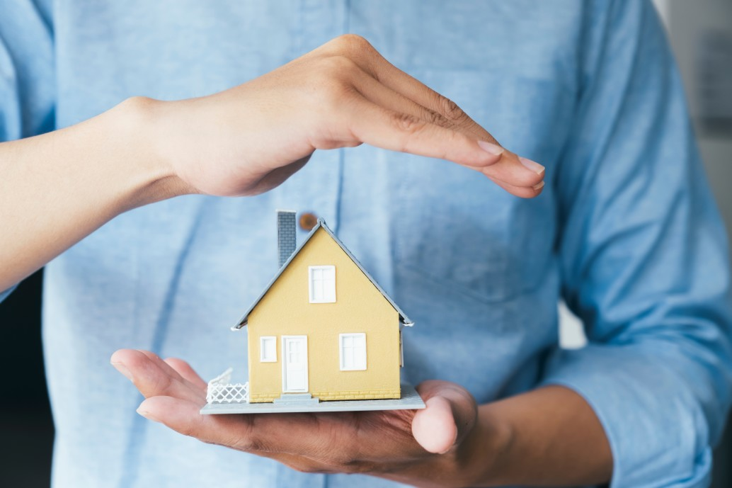 business-man-hand-hold-the-house-model-saving-small-house