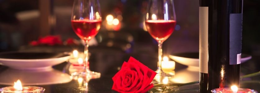 two wine glasses and roses on a candlelit table