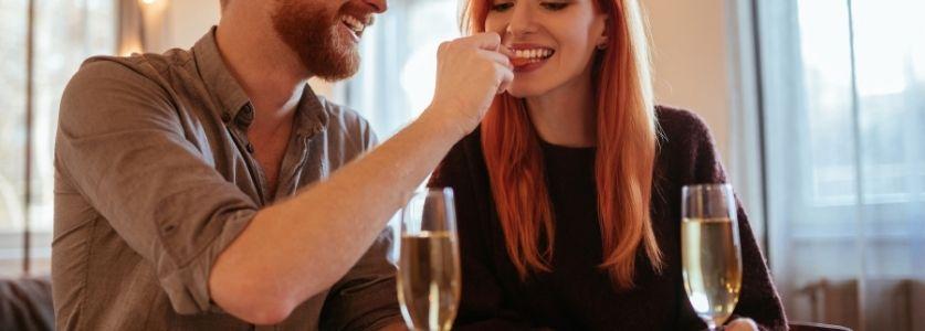 A man feeding his woman date finger food