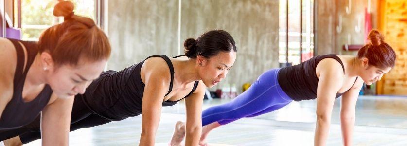 Three girls doing planks in a yoga studio