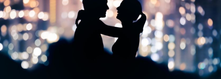 Two silhouettes hugging