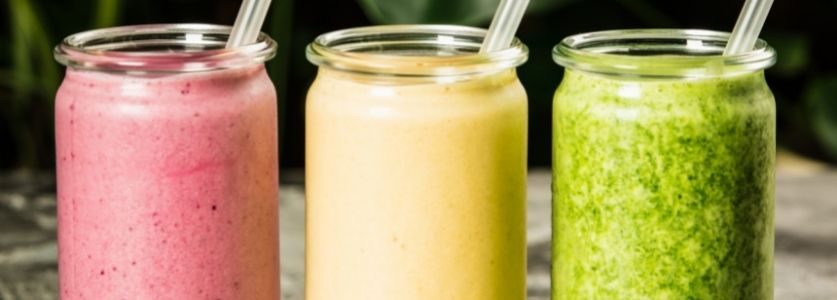 three different colored smoothies in row glasses