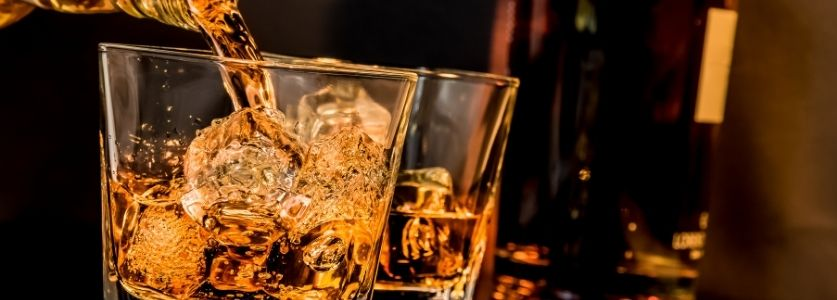 whiskey pouring into tumbler glass on the rocks