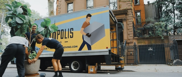 A moving truck and movers in the corner moving a big plant