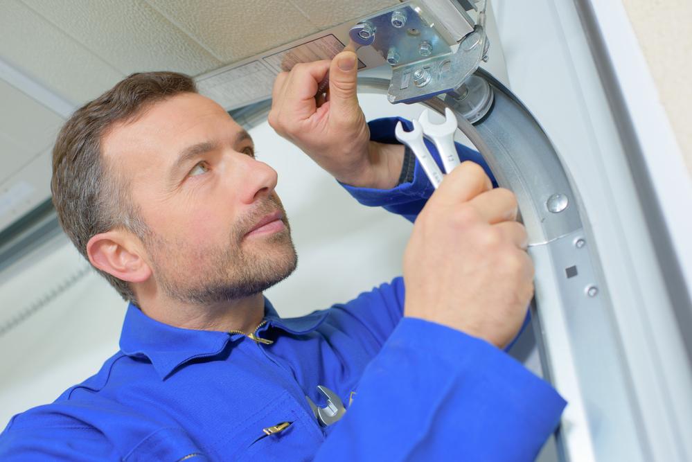 a scottsdale garage door repair man fixing a broken door