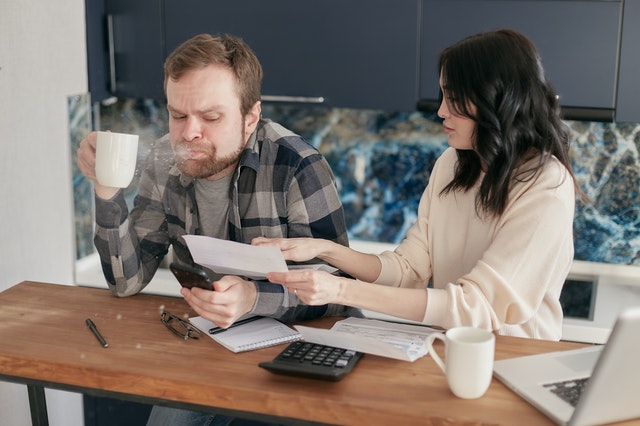 a couple going over their bills at the coffee table