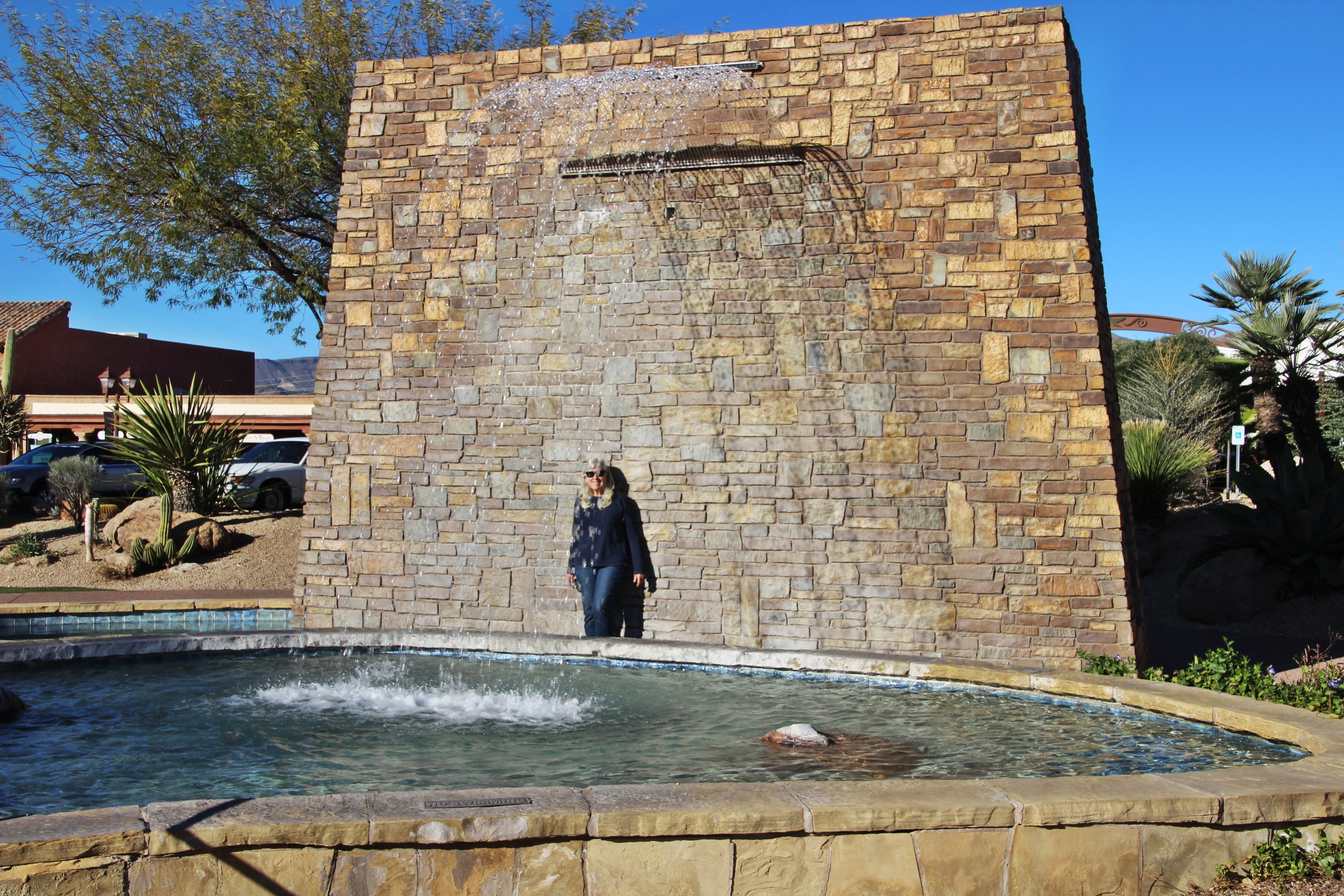 judy orr standing behind the water at the wall fountain