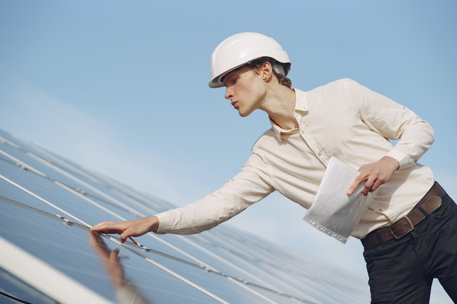 young man inspecting solar panels
