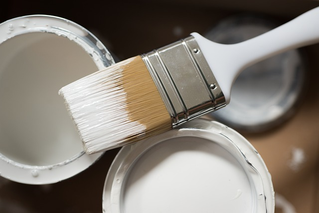 Buckets of white paint and a paint brush