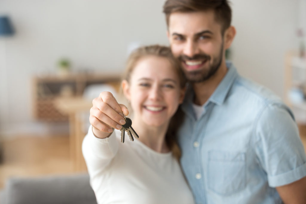 A happy couple holding the set of keys for their new home