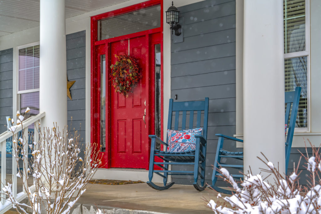 A front porch with a red door covered in snow