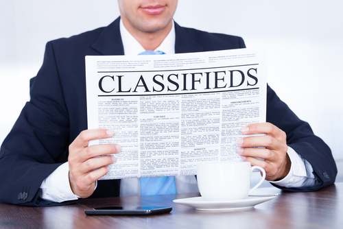 man holding classifieds newspaper