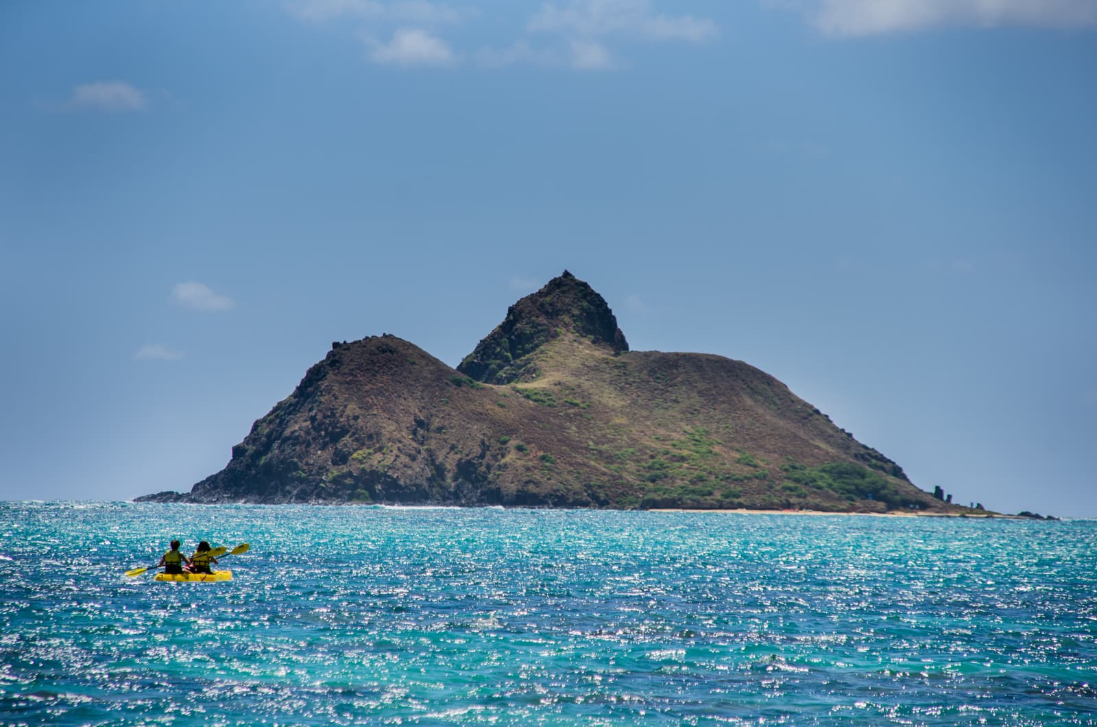 Two People In Boat Paddling To Small Island