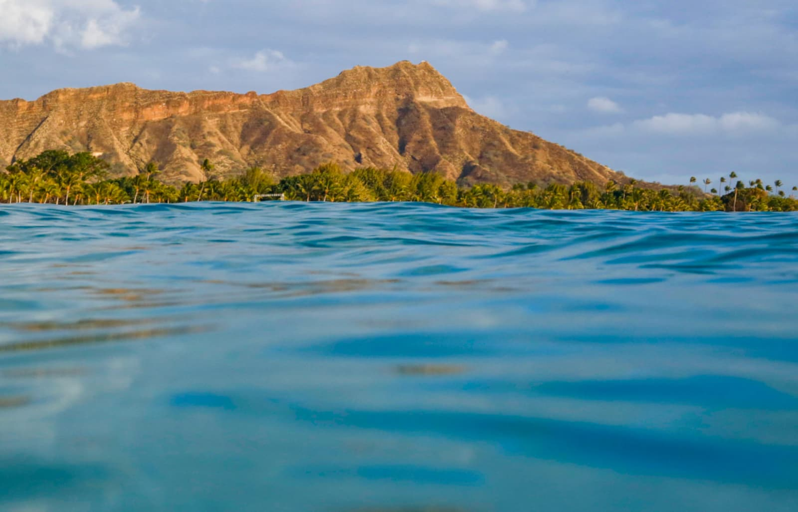 View from the ocean of a nearby island with a mountain range and palm trees