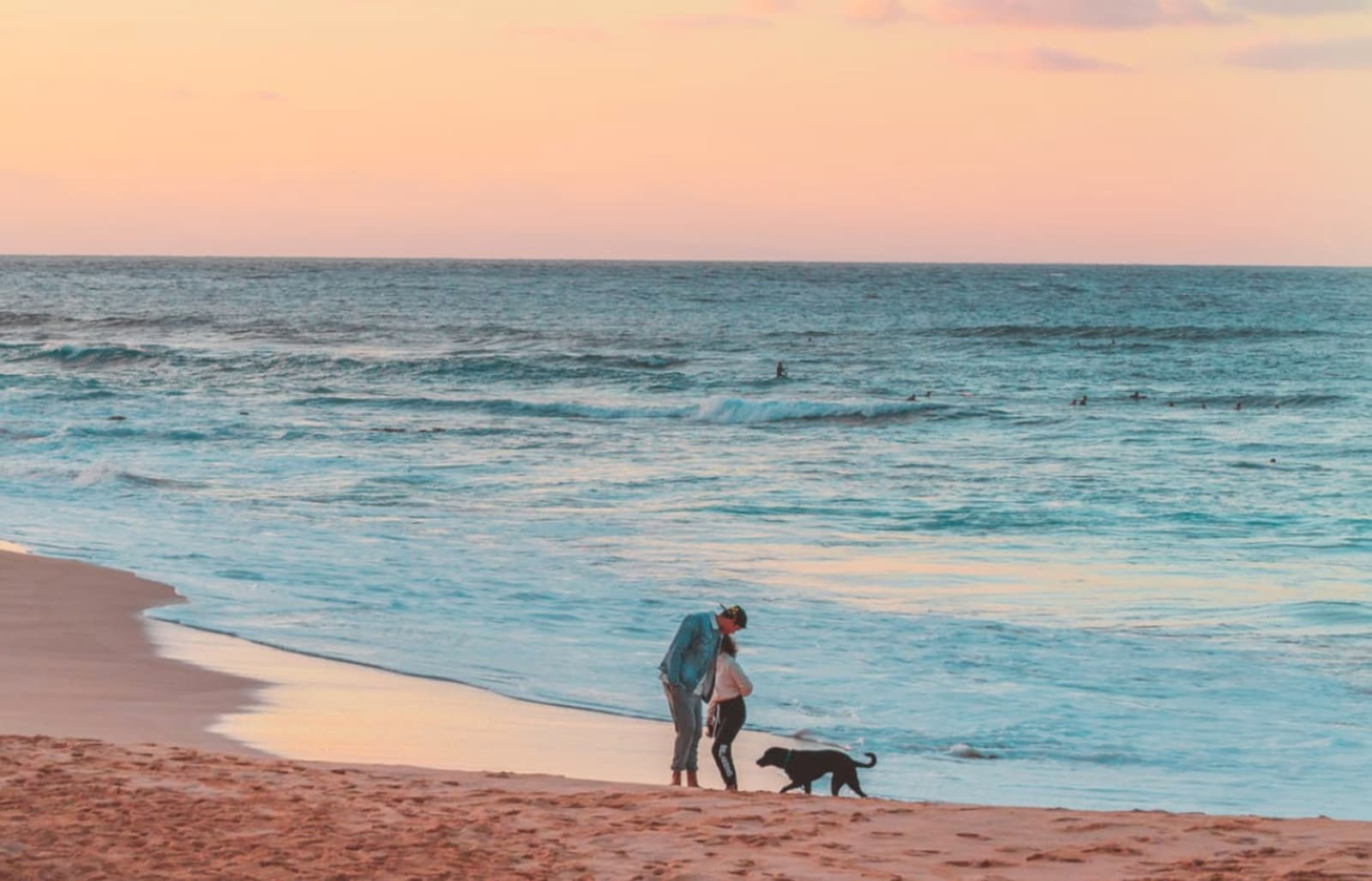 Beach near sunset or sunrise with man, woman, and dog in middle-distance