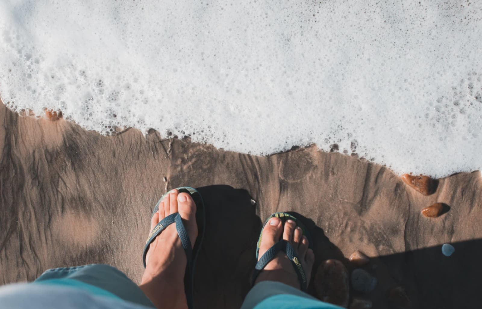 Point of view picture; looking down at a pair of feet in flipflops on a beach as the white foamy surf rolls in