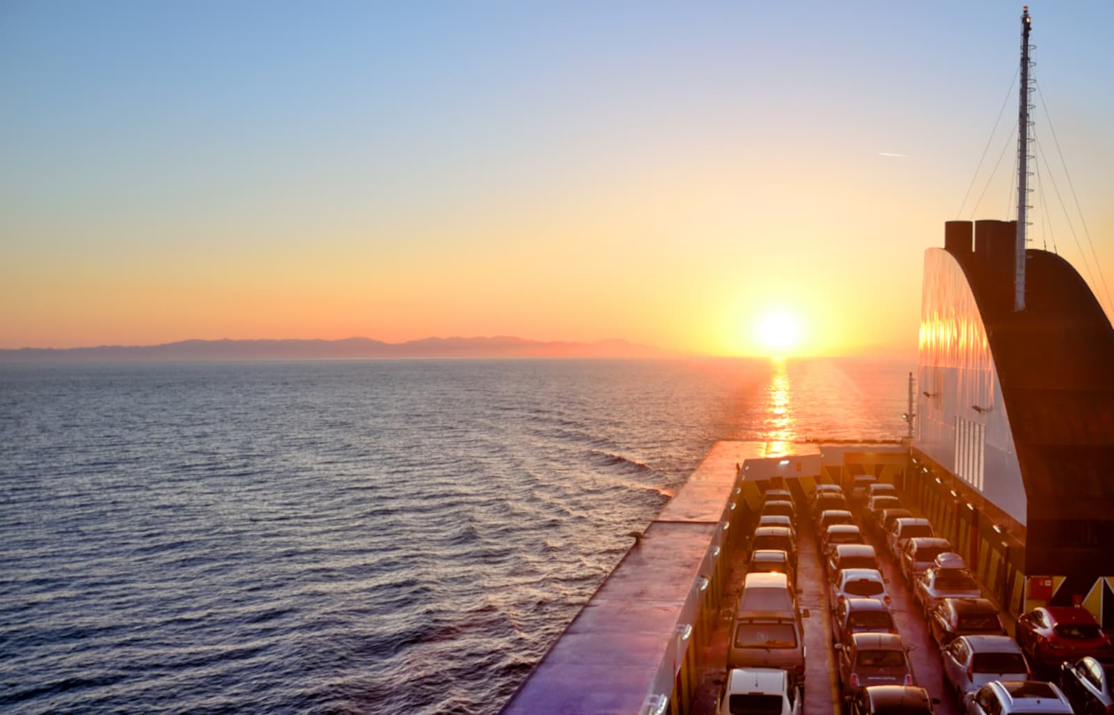A shipping vessel containing many cars at sea during ocean sunset/sunrise