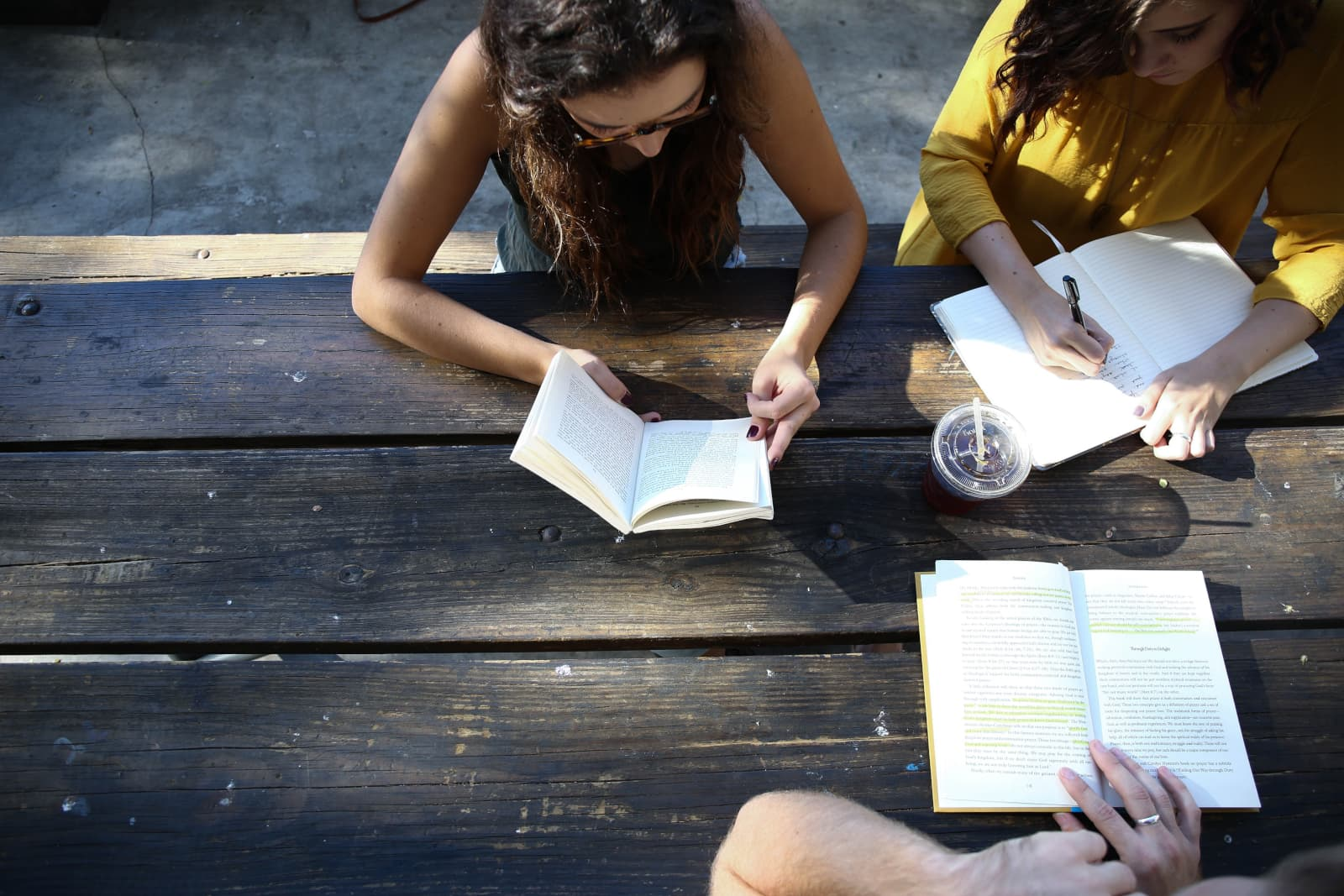 Three People Reading And Taking Notes At Picnic Table