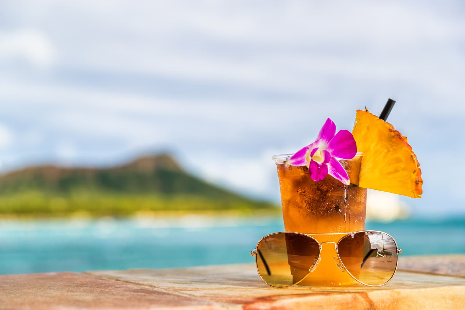 Drink and sunglasses with island in the background