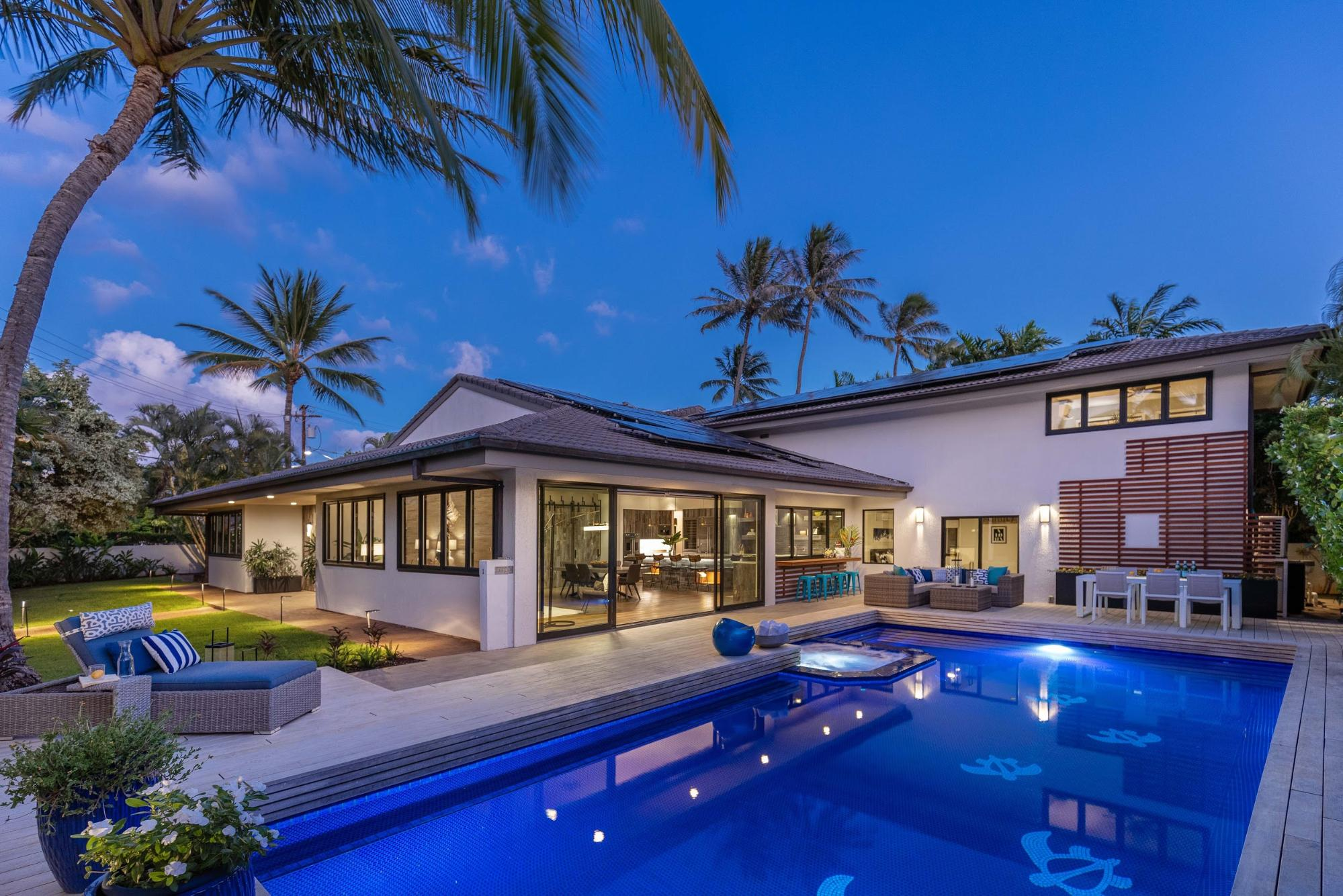 A view of a home in Kahala from the exterior. The visibile portion of the home includes a pool, pool furniture, large windows, and lots of greenery.