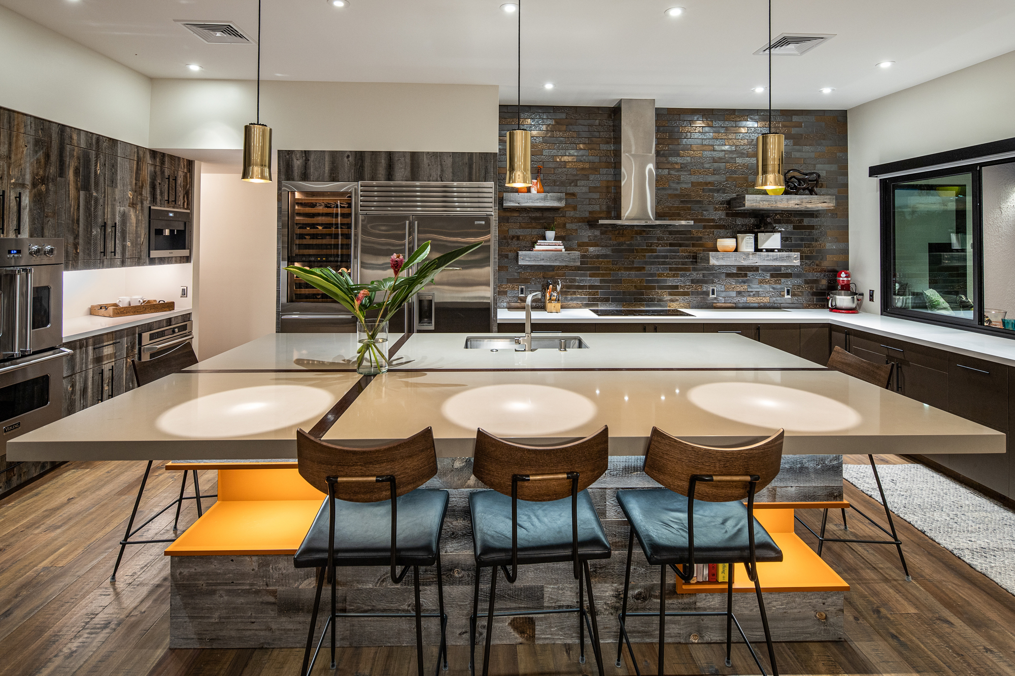 A luxurious kitchen with barstools, island with sink, stovetop with hood, and large fridge.