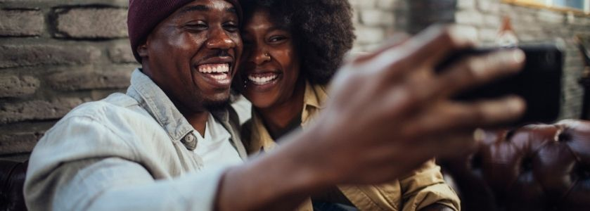 smiling couple on date taking selfie